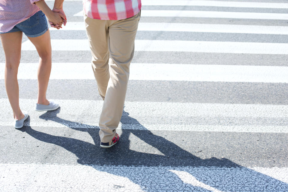 An unidentified couple walking on crosswalk while holding hands.