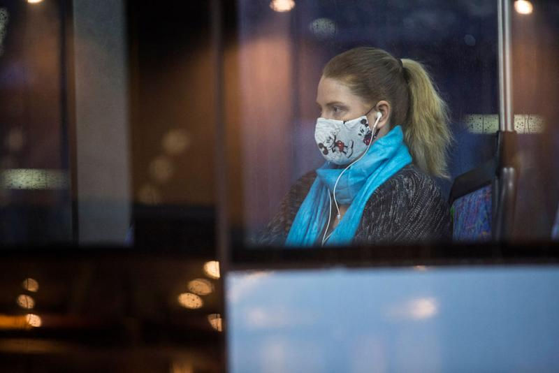 A female passenger wears a face mask while sitting on a bus in Sydney.