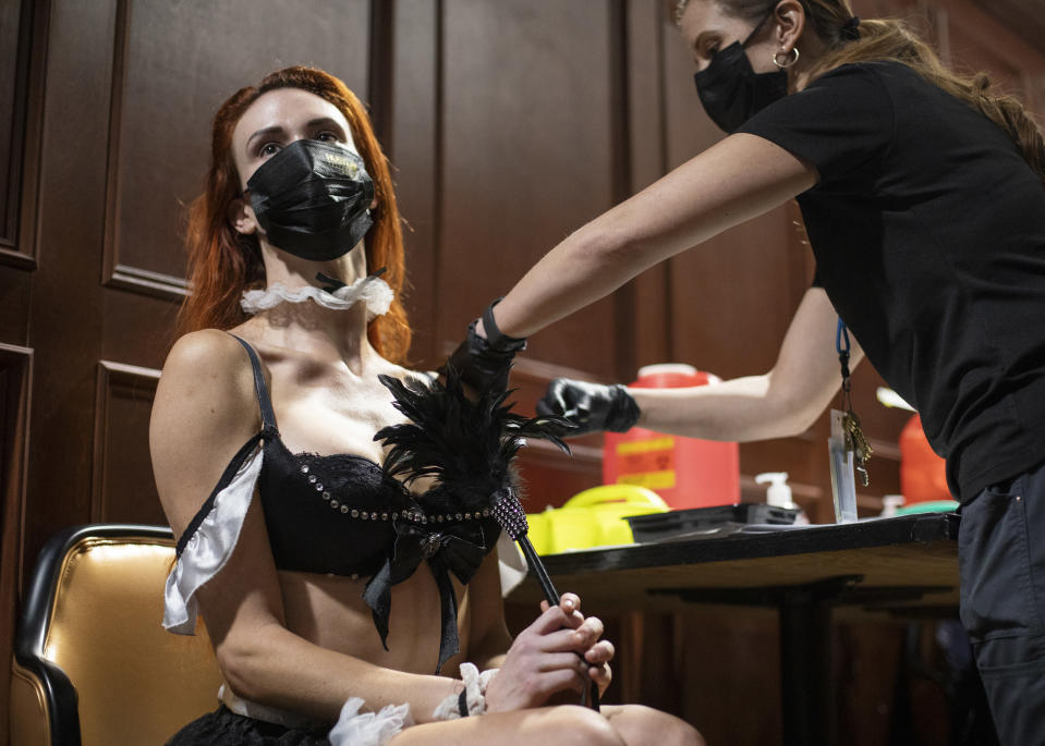 """FILE - In this May 21, 2021, file photo, JoJo Hamner, a cast member of the """"Sexxy After Dark: Where Dinner Meets Play"""" show, gets the Pfizer COVID-19 vaccine during a pop-up vaccine clinic at Larry Flynt's Hustler Club in Las Vegas. It's one of several methods health officials are employing here and across the country to bring vaccines directly to people to counter waning demand. In tiny towns, ballparks, strip clubs, and marijuana dispensaries, officials are setting up shop and offering incentives to entice people who so far have not gotten shots. (Ellen Schmidt/Las Vegas Review-Journal via AP, File)"""
