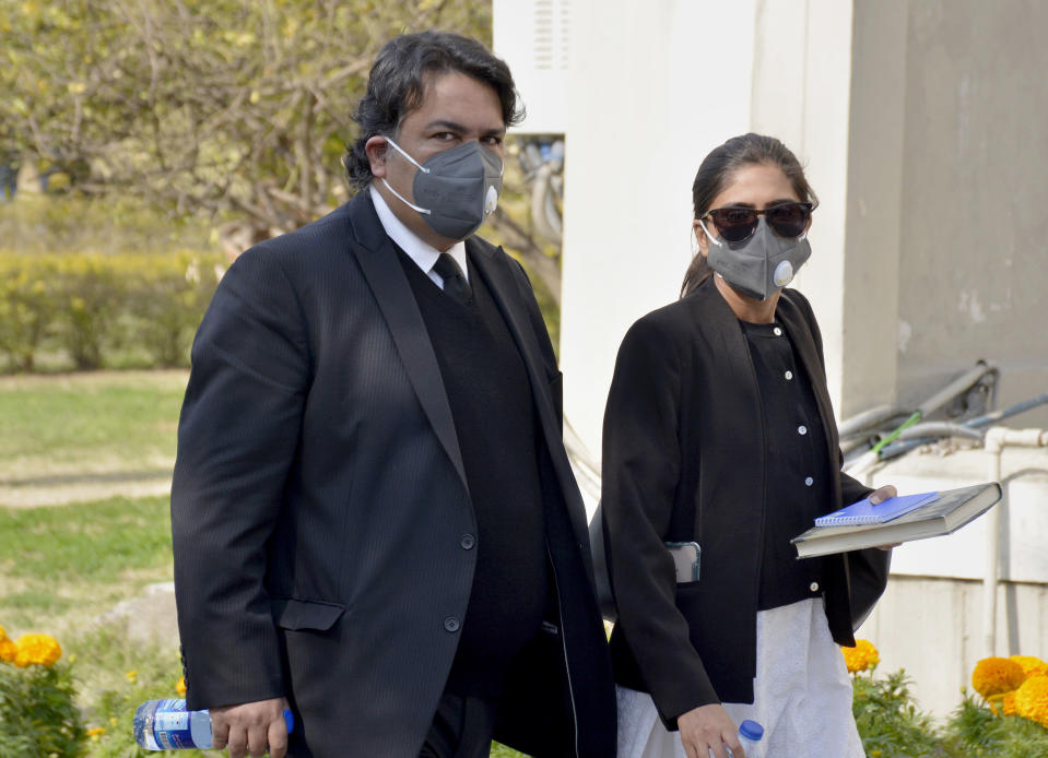 Faisal Siddiqi, left, a lawyer for the family of Daniel Pearl, an American reporter who was kidnapped and killed in Pakistan, arrives with his assistant at the Supreme Court for an appeal hearing in the Daniel Pearl case, in Islamabad, Pakistan, Thursday, Jan. 28, 2021. The court on Thursday has ordered the release of Pakistani man Ahmad Saeed Omar Sheikh convicted and later acquitted in the gruesome beheading of American journalist Pearl in 2002. The court also dismissed an appeal of Sheikh's acquittal by Pearl's family. (AP Photo/Waseem Khan)