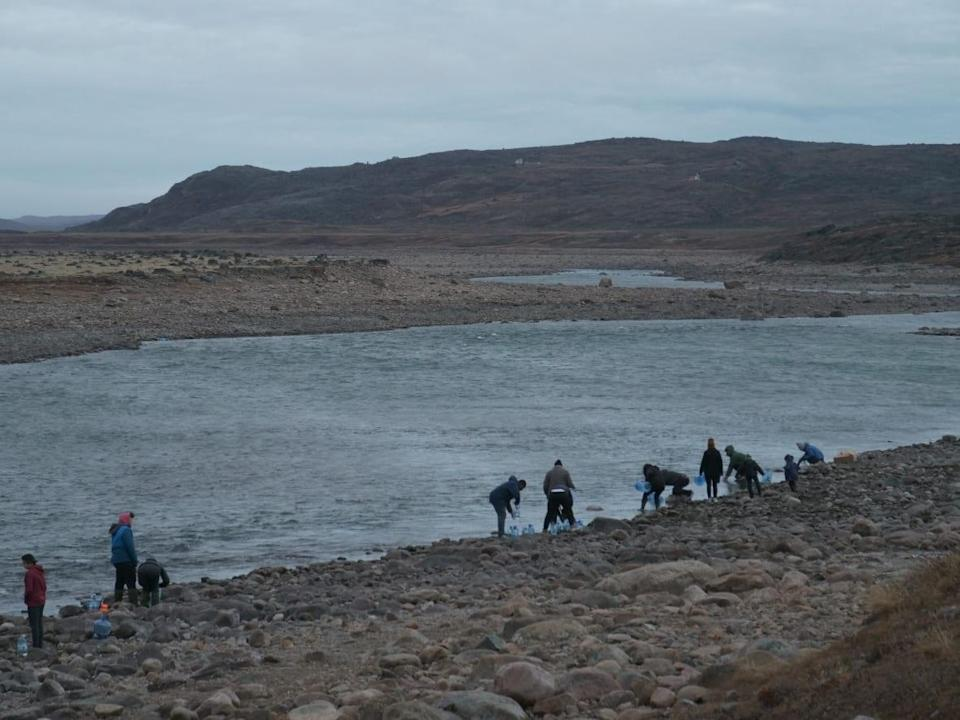 People in Iqaluit flocked to the nearby Sylvia Grinnell River to gather drinking water after learning that the city's tap water was unsafe to drink because of what appeared to be fuel contamination. Iqaluit's chief administrative officer said residents should boil river water for one minute to make sure it's safe for consumption. (David Gunn/CBC - image credit)