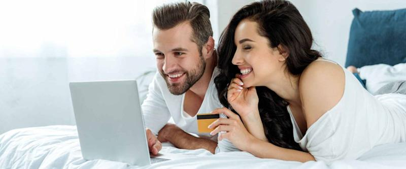 smiling young couple using laptop and holding credit card in bed, online shopping