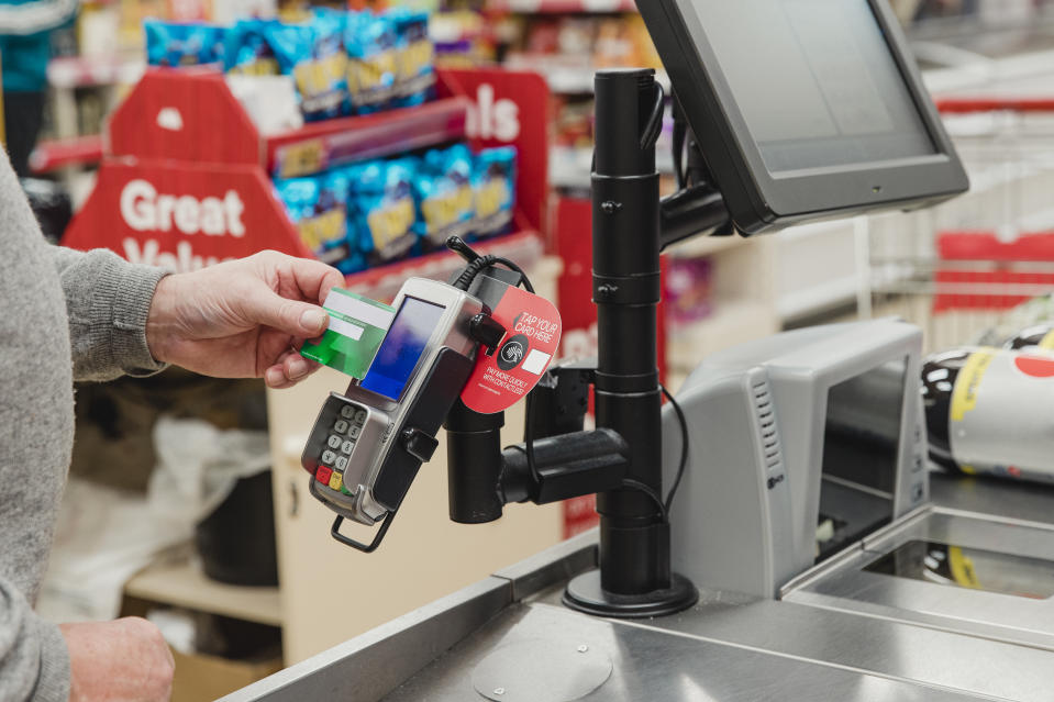 Close up shot of a senior man making a contactless payment at a supermarket till.