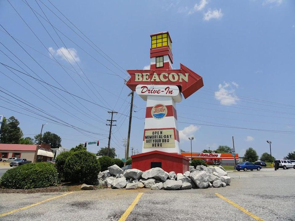 """<p>Beacon Drive-In opened in 1946, and this <a href=""""https://www.thedailymeal.com/cook/classic-southern-recipes-are-better-grandma-s-gallery?referrer=yahoo&category=beauty_food&include_utm=1&utm_medium=referral&utm_source=yahoo&utm_campaign=feed"""" rel=""""nofollow noopener"""" target=""""_blank"""" data-ylk=""""slk:Southern classic"""" class=""""link rapid-noclick-resp"""">Southern classic</a> has been dishing out fast food to drivers (and diners in indoor booths) ever since. It's perhaps best known for the """"a-plenty"""" option, which means your meal will come with piles of sweet onion rings and french fries. Like any true Southern spot, this place serves its can't miss sweet tea plenty sweet.</p>"""