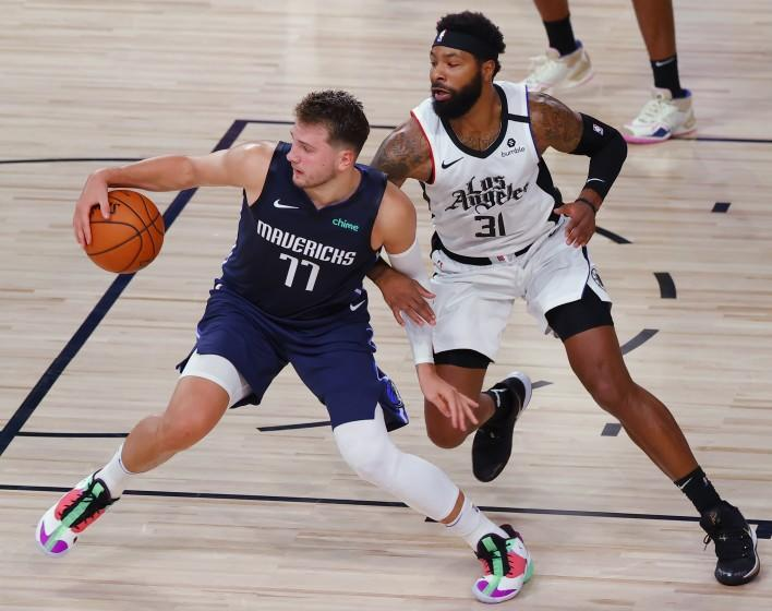 Dallas Mavericks' Luka Doncic is defended by Los Angeles Clippers' Marcus Morris Sr. during the fourth quarter of Game 4 of an NBA basketball first-round playoff series, Sunday, Aug. 23, 2020, in Lake Buena Vista, Fla. (Kevin C. Cox/Pool Photo via AP)