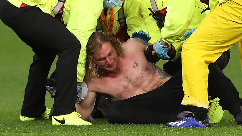 Pitch invader Jesse Hayer is pictured being tackled to the ground by security at Optus Stadium.