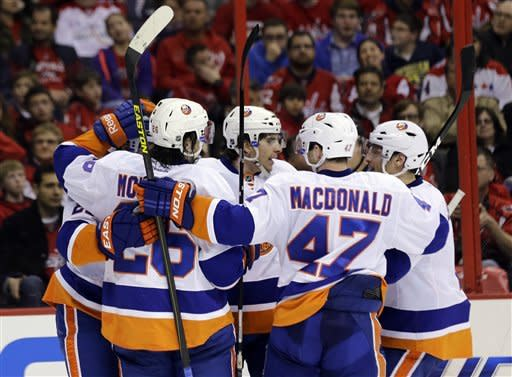New York Islanders center John Tavares, center, celebrates with teammates after his go-ahead goal in the third period of an NHL hockey game against the Washington Capitals on Tuesday, March 26, 2013 in Washington. The Islanders won 3-2. (AP Photo/Alex Brandon)