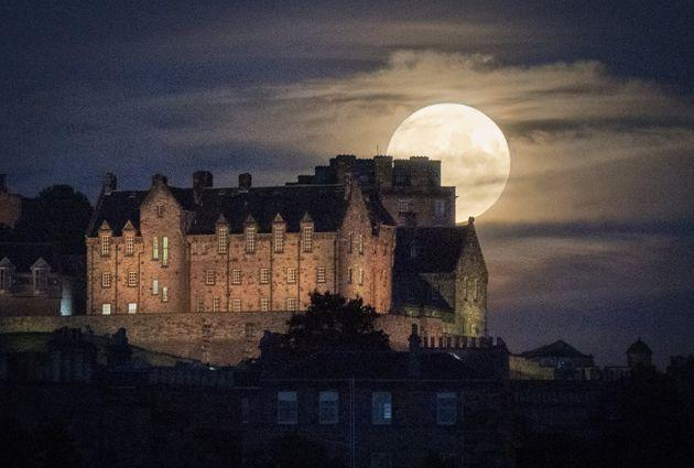 The full moon rises behind Edinburgh Castle. Otherwise known as Thunder Moon, the July full moon is synonymous with summer storms (Photo: Jane Barlow - PA Images via Getty Images)