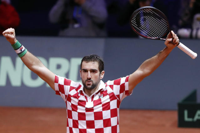 Croatia's Marin Cilic raises his arms after defeating France's Jo-Wilfried Tsonga during the Davis Cup final between France and Croatia, Friday, Nov. 23, 2018 in Lille, northern France. Croatia is within one point of a second Davis Cup title after Borna Coric and Marin Cilic dispatched their French rivals in the opening singles matches of the final to take a 2-0 lead. (AP Photo/Thibault Camus)