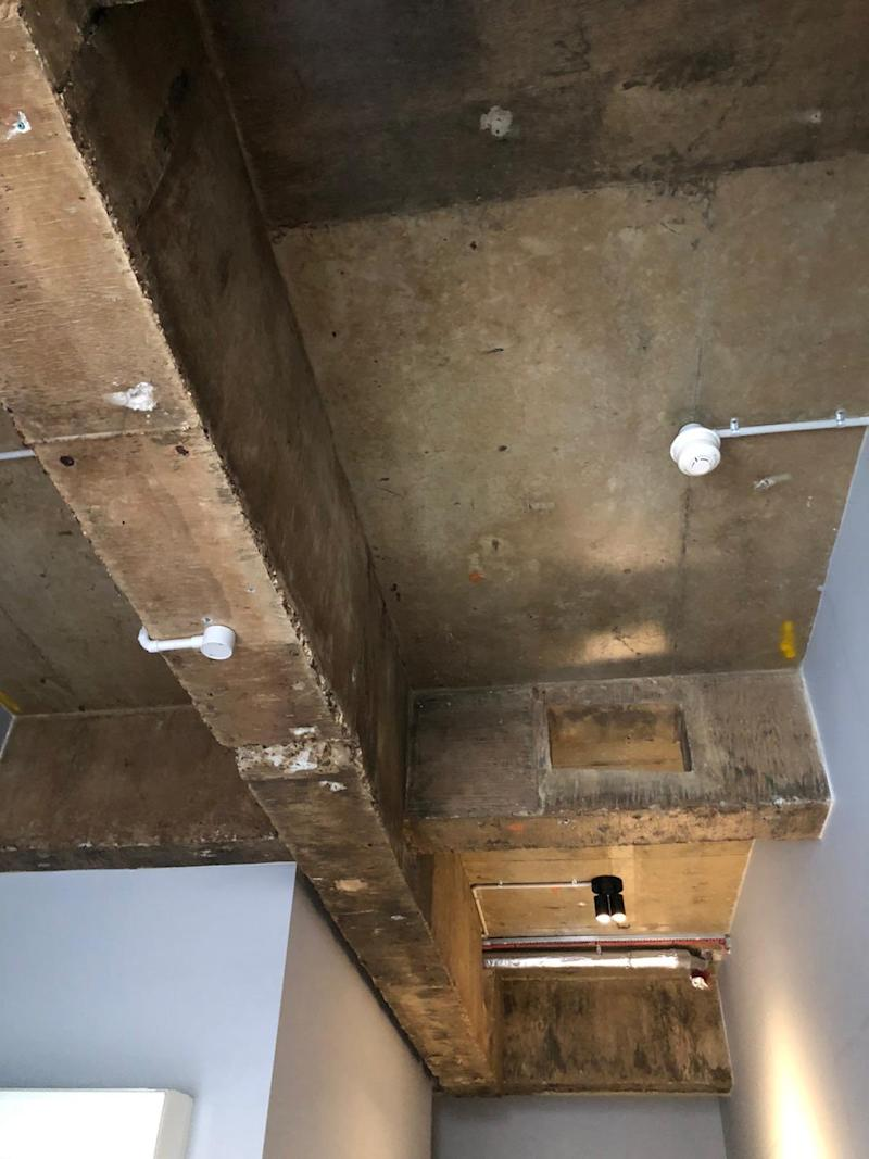 Image shows exposed pipes and naked light bulb on isolation hotel room ceiling