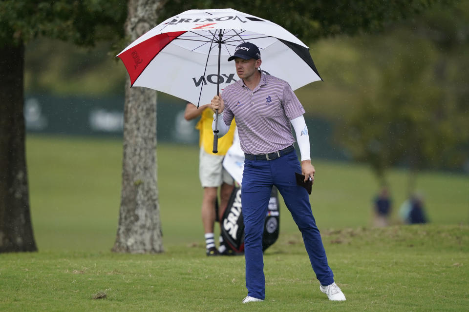 Jared Wolfe steps out with his umbrella as rain begins to fall during the first round of the Sanderson Farms Championship golf tournament in Jackson, Miss., Thursday, Sept. 30, 2021. The rain was short-lived and did not cause a weather delay. (AP Photo/Rogelio V. Solis)