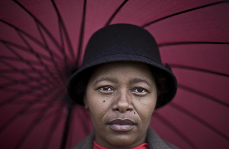 South African mourner, Charlotte Nthetea, 35, poses for a picture, while waiting with other mourners for hours to catch a bus to see the body of former President Nelson Mandela, in Pretoria, South Africa, Thursday, Dec. 12, 2013. Nelson Mandela is gone, but many mourners waiting patiently for a chance to see Mandela for a last time on Thursday said they retain high hopes about South Africa's future. If the heady optimism of the days when South Africa's peaceful transformation to democracy two decades ago has been diminished by time and economic challenges, many still believe the years ahead can be fruitful, with growing opportunity. (AP Photo/Muhammed Muheisen)