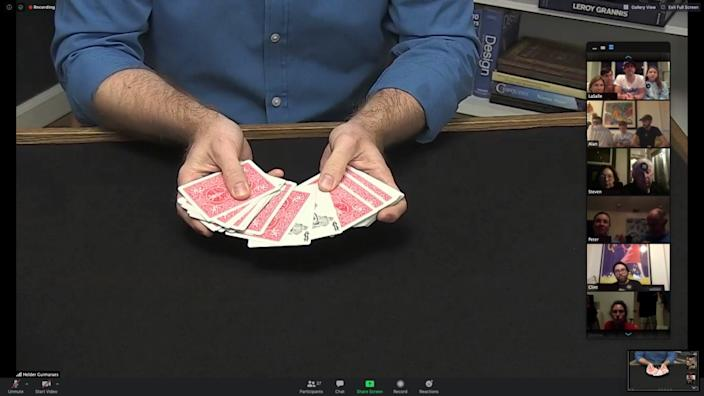 Magician Helder Guimarães holds out a deck of cards.