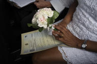 A bride holds a bouquet during her drive-thru wedding at the registry office of the neighborhood of Santa Cruz in Rio de Janeiro, Brazil, Thursday, May 28, 2020. Couples have begun turning to this unconventional union since the COVID-19 pandemic started battering Brazil. (AP Photo/Silvia Izquierdo)