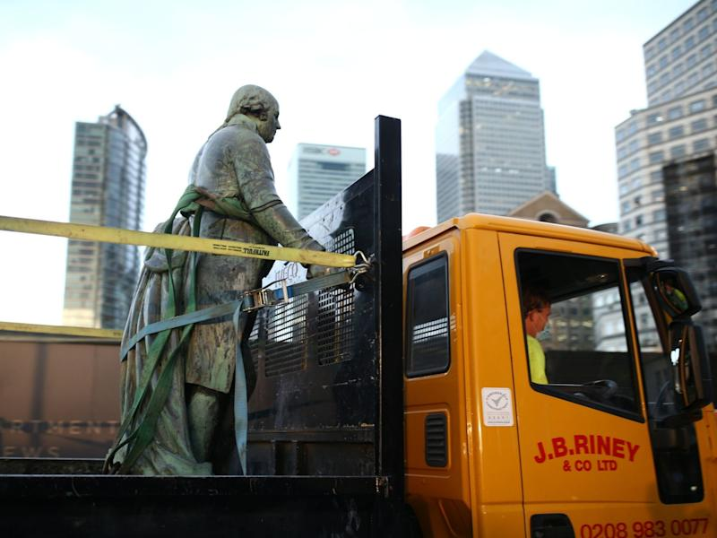 Workers take down a statue of slave owner Robert Milligan at West India Quay, in east London's Docklands (PA)