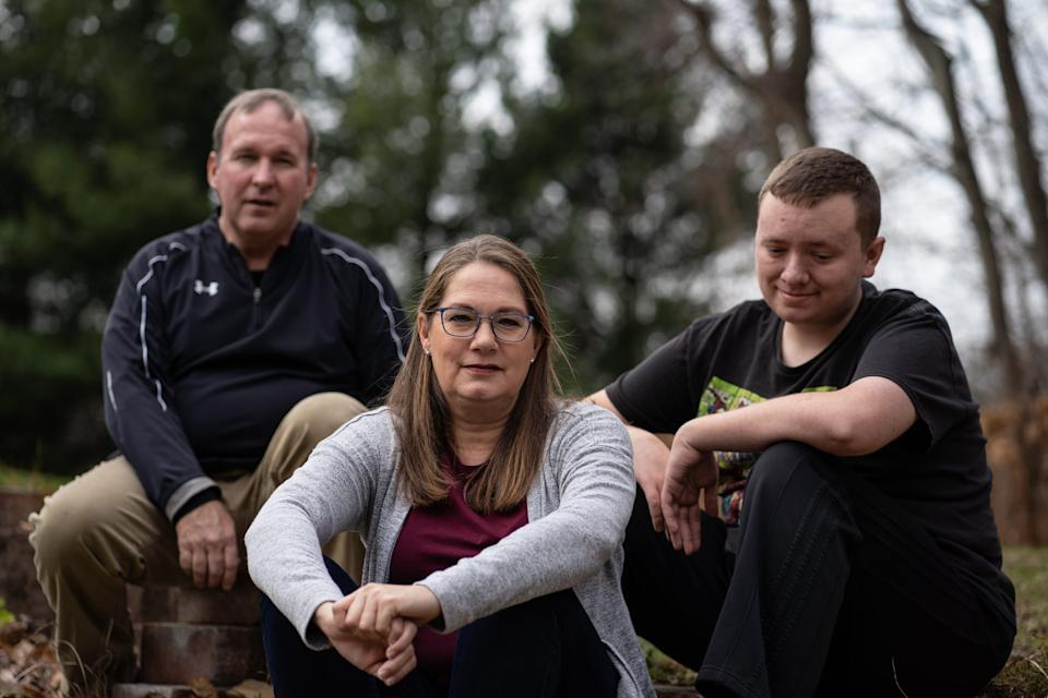 Pam Warfle, center, sits with her son Jonathan Warfle and husband Mark Warfle at their Michigan home this month. She has twice faced the unthinkable due to COVID-19, leaving both her son and then her 83-year-old mother at the hospital.