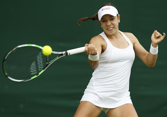 Sharon Fichman of Canada plays a return to Timea Bacsinszky of Switzerland during their first round match at the All England Lawn Tennis Championships in Wimbledon, London, Tuesday, June 24, 2014. (AP Photo/Alastair Grant)