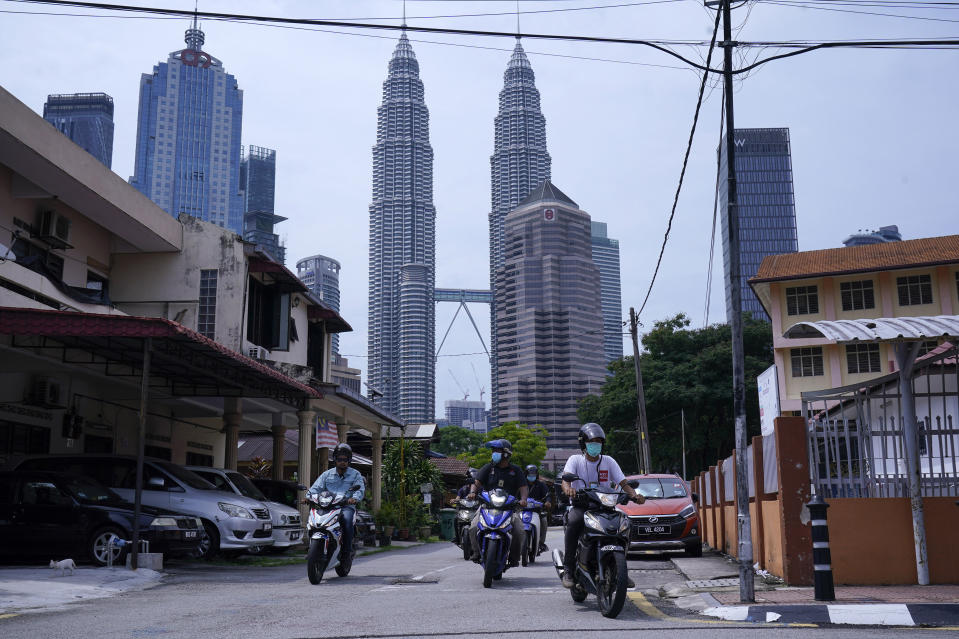 Motorist make their way through Kampung Baru, a traditional Malay village in Kuala Lumpur, Malaysia, Tuesday, April 14, 2020. The Malaysian government issued a restricted movement order to the public till April 15, to help curb the spread of the new coronavirus. The new coronavirus causes mild or moderate symptoms for most people, but for some, especially older adults and people with existing health problems, it can cause more severe illness or death. (AP Photo/Vincent Thian)