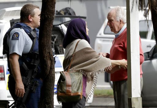 Police escort people away from outside a mosque following the attack (AP)