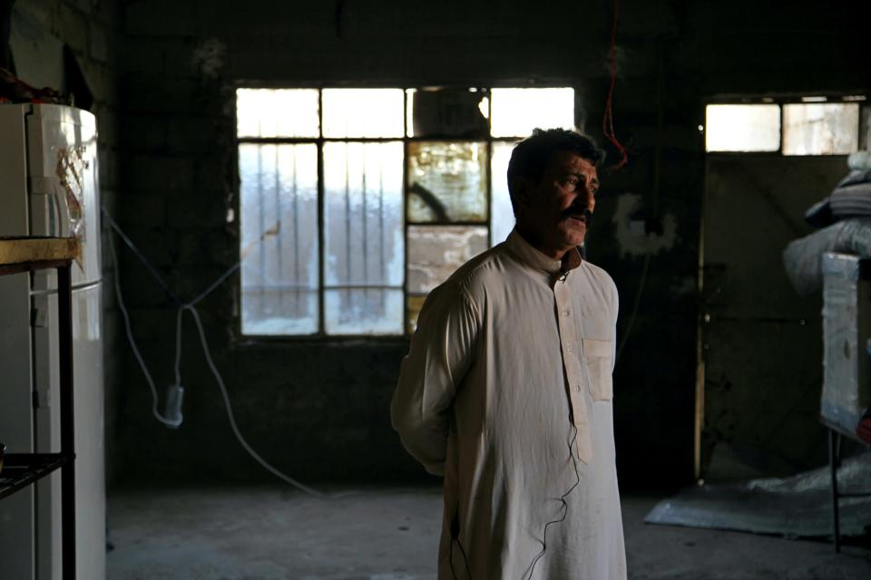 Ghanem Khalaf stands inside his unfinished home after returning from a closed displacement camp, in the Hay Tanak slum of Mosul, Iraq, Nov. 28, 2020. A push by the Iraqi government to close displacement camps by the end of the year threatens to leave tens of thousands of people homeless and without aid during a pandemic and at the onset of winter. Aid groups say the haphazard implementation of the policy is fueling more displacement and resentment. (AP Photo/Samya Kullab)