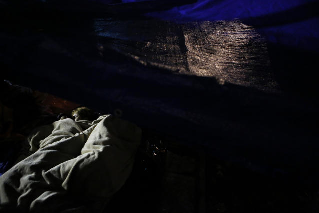 <p>Family members who have been camped out for days nap under a tarp alongside the collapsed office building where they believe their relatives are trapped, in the Roma Norte neighborhood of Mexico City, just after midnight on Sept. 23, 2017, more than three days after a 7.1 magnitude earthquake toppled buildings. (Photo: Rebecca Blackwell/AP) </p>