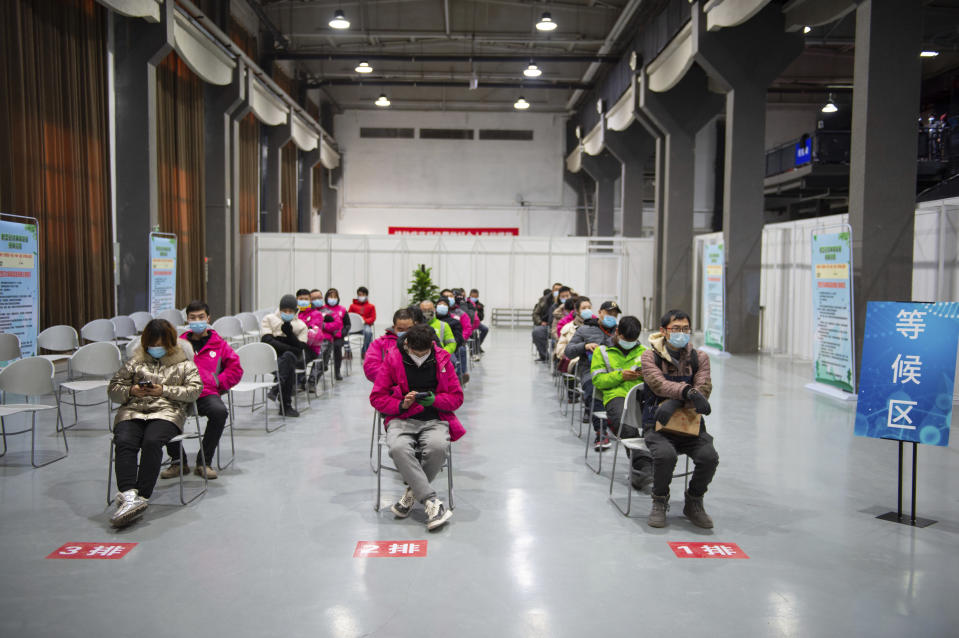 In this photo released by Xinhua News Agency, residents wait to receive their COVID-19 vaccinations at a temporary vaccination site in Beijing, Saturday, Jan. 2, 2021. China authorized its first homegrown COVID-19 vaccine for general use on Dec. 31, 2020, adding another shot that could see wide use in poorer countries as the virus surges back around the globe. (Chen Zhonghao/Xinhua via AP)