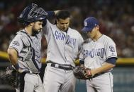 San Diego Padres pitcher Gerardo Reyes, right, pauses with third baseman Manny Machado and catcher Austin Hedges, left, during the sixth inning of the team's baseball game against the Arizona Diamondbacks on Saturday, April 13, 2019, in Phoenix. (AP Photo/Ross D. Franklin)