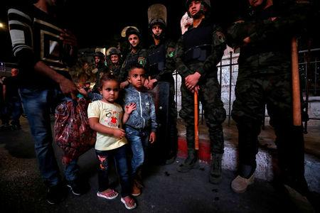 Children walk as members of Palestinian security forces stand guard during a protest calling on President Mahmoud Abbas to end financial sanctions on Palestinians in Gaza, in Ramallah, in the occupied West Bank