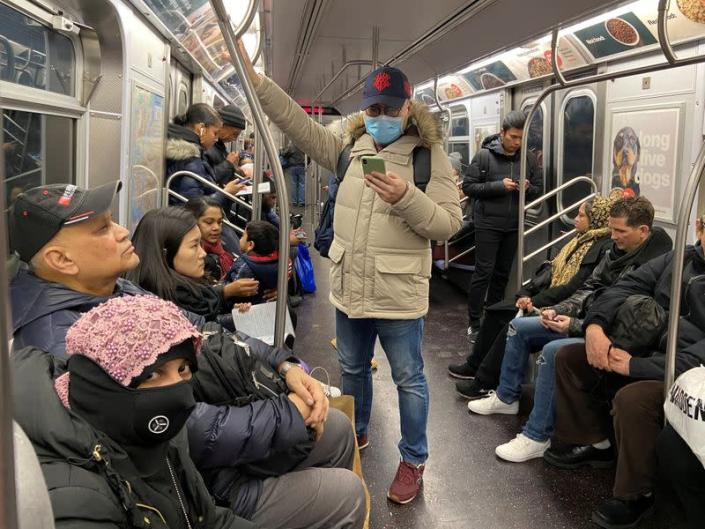 A man with a face mask rides the subway in the Queens borough of New York Cit