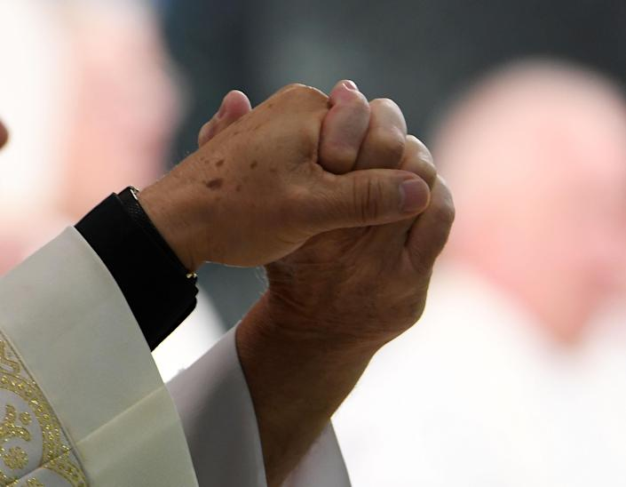 <p>Members of the clergy hold hands during a vigil at Guardian Angel Cathedral for the victims of the Route 91 Harvest country music festival shootings on October 2, 2017 in Las Vegas, Nevada. (Photo: Denise Truscello/Getty Images) </p>