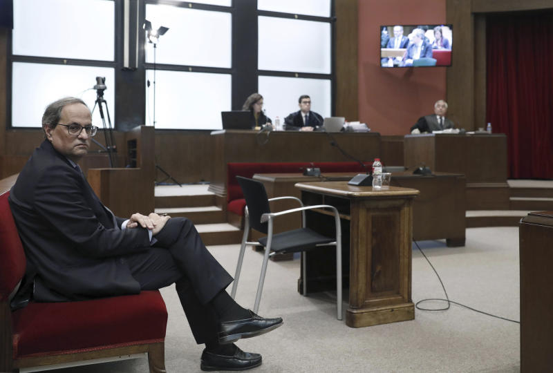 Catalan President Quim Torra sits in court in Barcelona, Spain, Monday, Nov.18, 2019. The pro-independence regional president of Catalonia is standing trial for allegedly disobeying Spain's electoral board by not removing pro-secession symbols from public buildings during an election campaign. Quim Torra could be declared unfit to hold public office for a period of time if found guilty in the trial that started Monday. (Andreu Dalmau, Pool photo via AP)