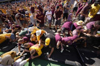 Minnesota fans collapse the fence around the field while congratulating players after the second half of an NCAA college football game against Colorado Saturday, Sept. 18, 2021, in Boulder, Colo. Minnesota won 30-0. (AP Photo/David Zalubowski)