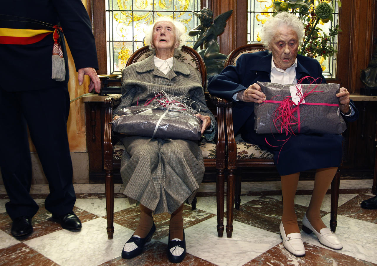 Marie (R) and Gabrielle Vaudremer, 100-year-old Belgian twins, receive gifts as they celebrate their birthday at the Chateau Sous-Bois retirement home in Spa October 2, 2010. Marie and Gabrielle were born in 1910 and are the world's oldest pair of twin sisters, according to the Guinness World Records. REUTERS/Thierry Roge