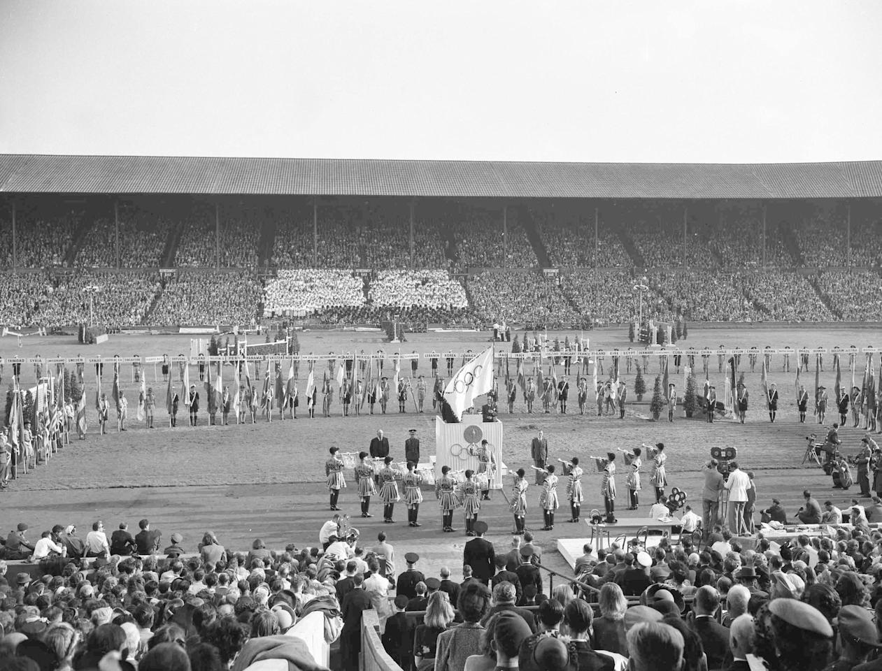 Britain's Sir Frederick Wells, Lord Mayor of London, right on podium holds the Olympic Flag, whilst Sigfrid J. Edstroem, President of the International Committee, obscured by flag, closes the XIV Olympic Games at Wembley Stadium, London, Aug. 14, 1948. Standing right of podium is Lord Burghley, Chairman of the organising committee of the London Olympics. Royal State Trumpeters wait to play a fanfare, left. (AP Photo)