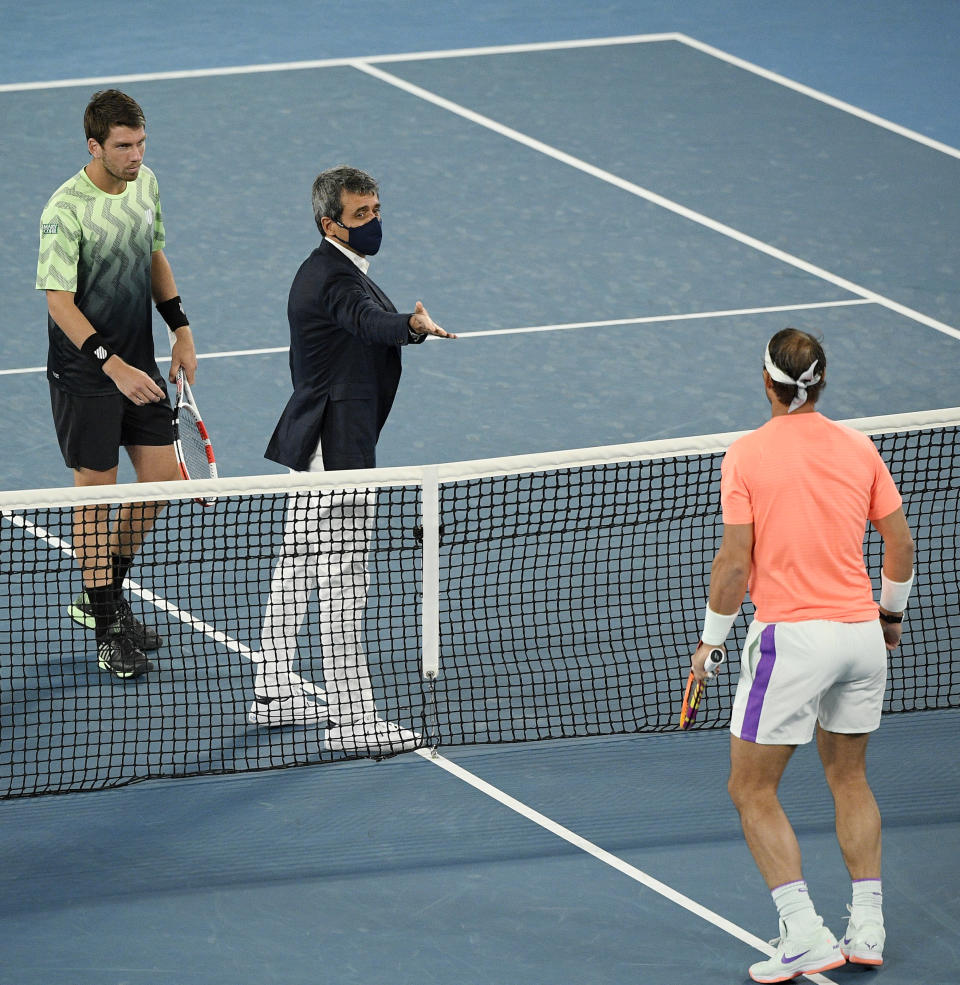 Spain's Rafael Nadal, right, and Britain's Cameron Norrie, left, meet at the net for the coin toss before their third round match a the Australian Open tennis championships in Melbourne, Australia, Saturday, Feb. 13, 2021. (AP Photo/Andy Brownbill)