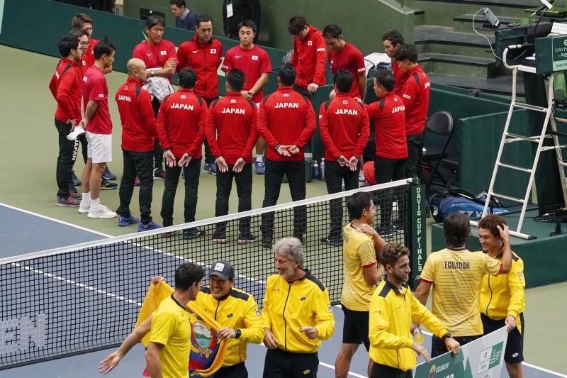 Ecuador's team, forehand, celebrates after beating Japan, rear, during their Davis Cup qualifier in Miki, Hyogo prefecture, western Japan, Saturday, March 7, 2020.  With no fans in the stands to give host Japan a boost, Ecuador took an insurmountable 3-0 lead on Saturday to secure a place in November's Davis Cup Finals in Madrid.(Nobuki Ito/Kyodo News via AP)