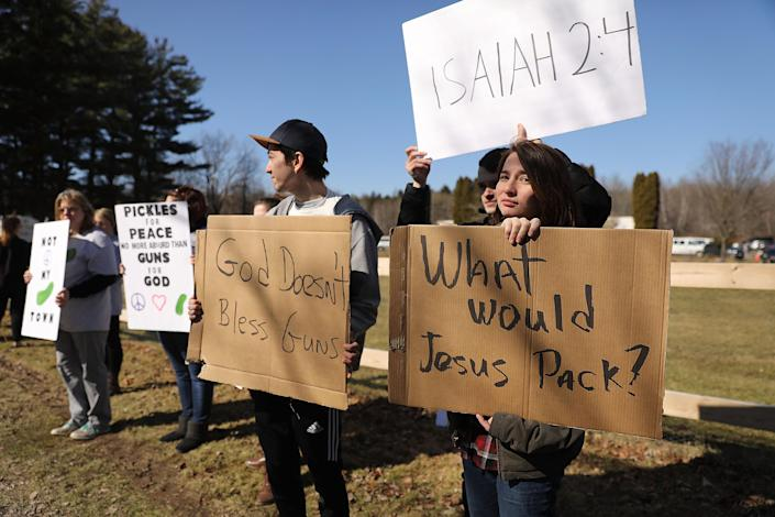 <p>Anti-gun protesters stand outside as couples with AR-15 rifles and other guns participate in a ceremony at the World Peace and Unification Sanctuary in Newfoundland, Pennsylvania on February 28, 2018 in Newfoundland, Pennsylvania. (Photo: Spencer Platt/Getty Images) </p>