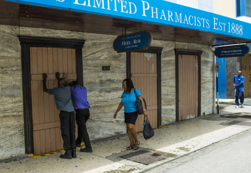 Residents board up a storefront pharmacy as they prepare for the arrival of Tropical Storm Dorian, in Bridgetown, Barbados, Monday, Aug. 26, 2019. Much of the eastern Caribbean island of Barbados shut down on Monday as Dorian approached the region and gathered strength, threatening to turn into a small hurricane that forecasters said could affect the northern Windward islands and Puerto Rico in upcoming days. (AP Photo/Chris Brandis)