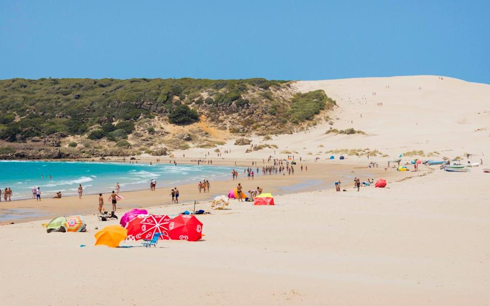 white beach with sand dunes and colourful parasols - Universal Images Group Editorial