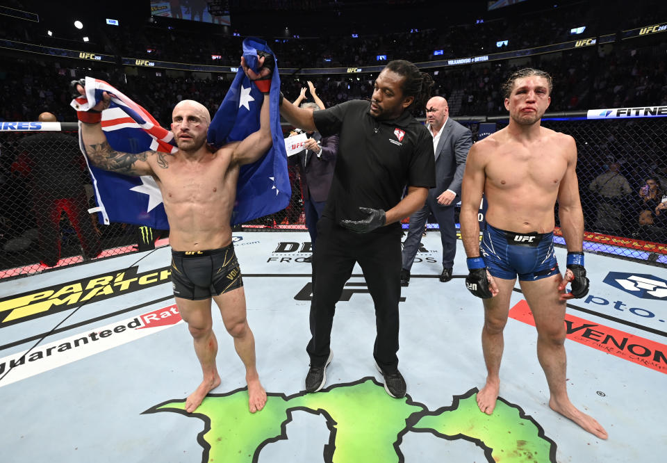 Alexander Volkanovski (pictured left) has his hand raised after he won his fight over Brian Ortega (pictured right) in their UFC featherweight championship fight during the UFC 266 event.