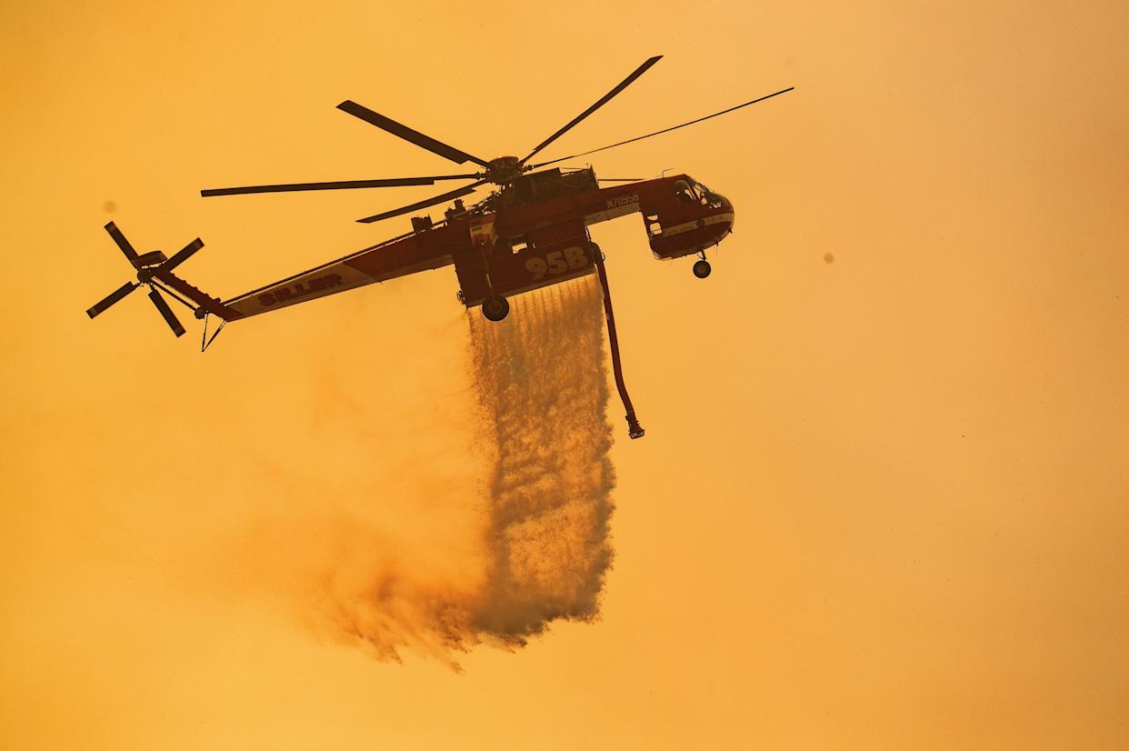 A helicopter drops water on a burning hillside during the Mendocino Complex Fire near Finley, California.
