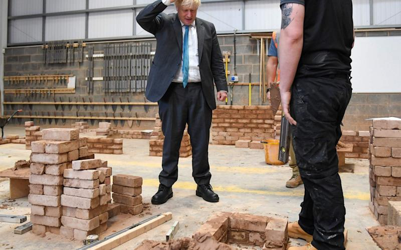 Boris Johnson turning his hand to bricklaying during a visit to Exeter College today - Finnbarr Webster/AFP