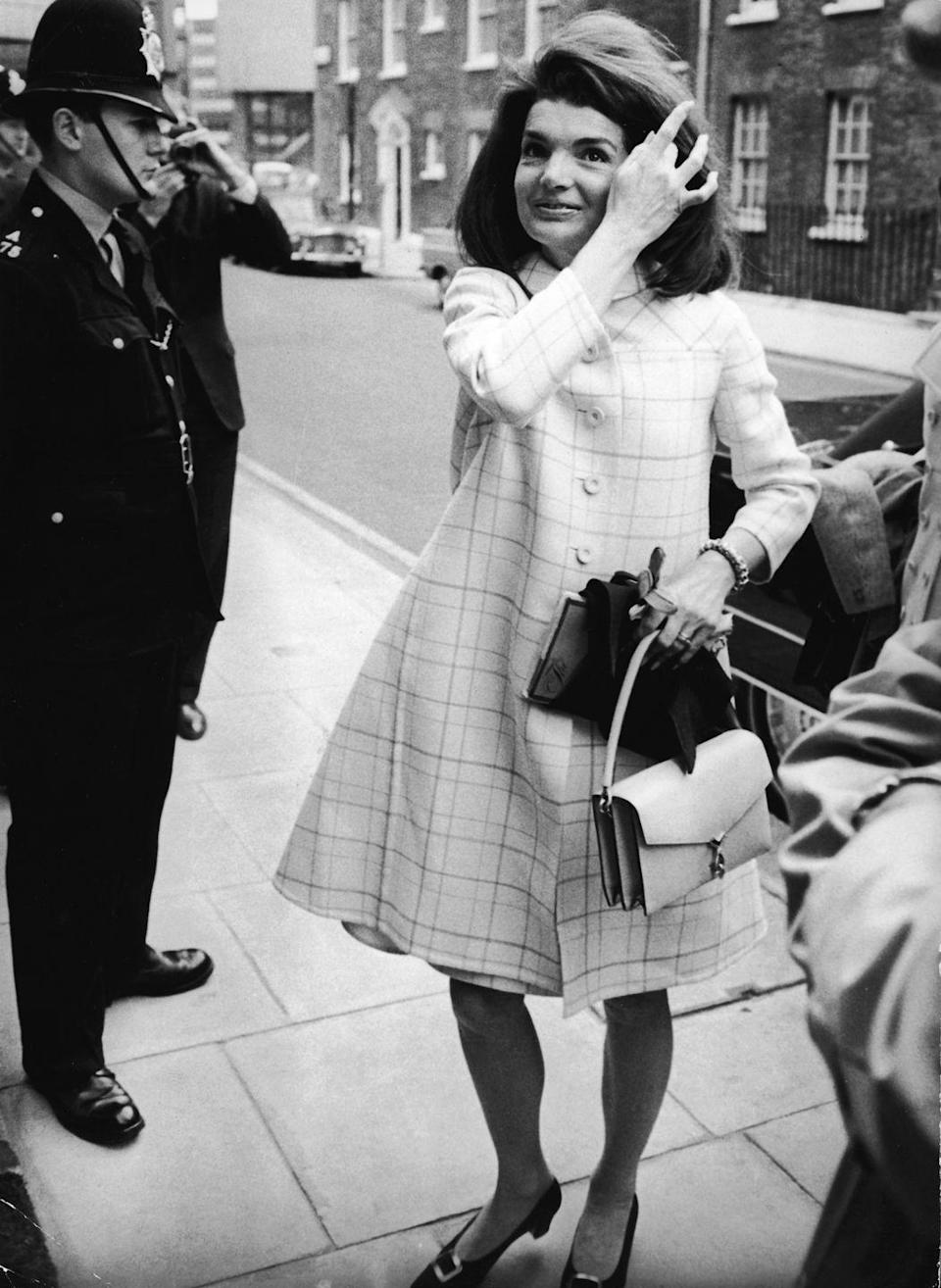 <p>Jackie composes herself as she arrives at her younger sister's London home in 1966. She looked stylish in a white tattersall plaid coat. </p>