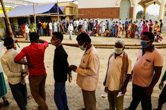 Voters stand in queues to cast their votes outside a polling booth during first phase of elections in West Bengal state in Medinipur, India, Saturday, March 27, 2021. Voting began Saturday in two key Indian states with sizeable minority Muslim populations posing a tough test for Prime Minister Narendra Modi's popularity amid a months-long farmers' protest and the economy plunging with millions of people losing jobs because of the coronavirus pandemic. (AP Photo/Bikas Das)