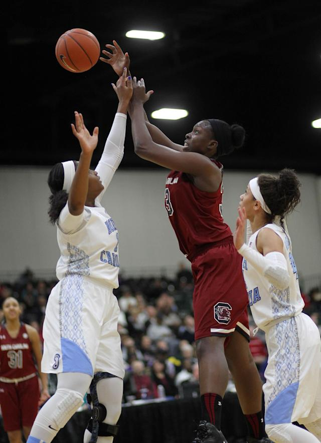 South Carolina's Elem Ibiam, center, has her shot blocked by North Carolina Stephanie Mavunga (1) in first-half action during an NCAA college basketball game in Myrtle Beach, S.C., Wednesday, Dec. 18, 2013. (AP Photo/Willis Glassgow)