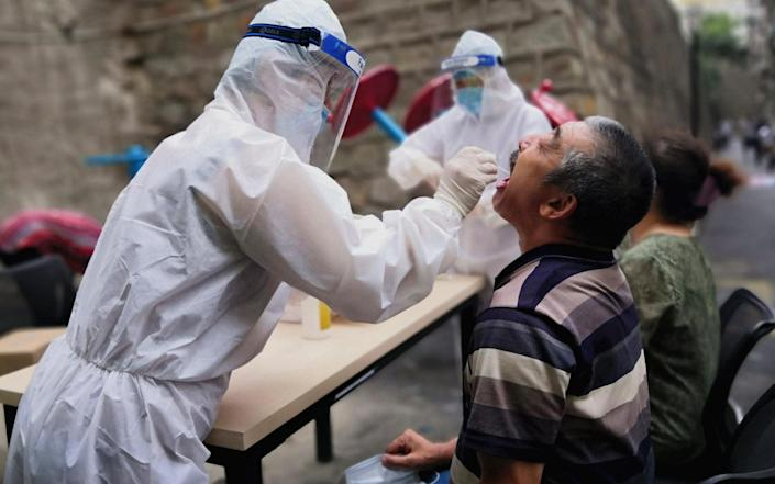 A medical worker swabs a citizen in Xinjiang's capital Urumqi - China News Service