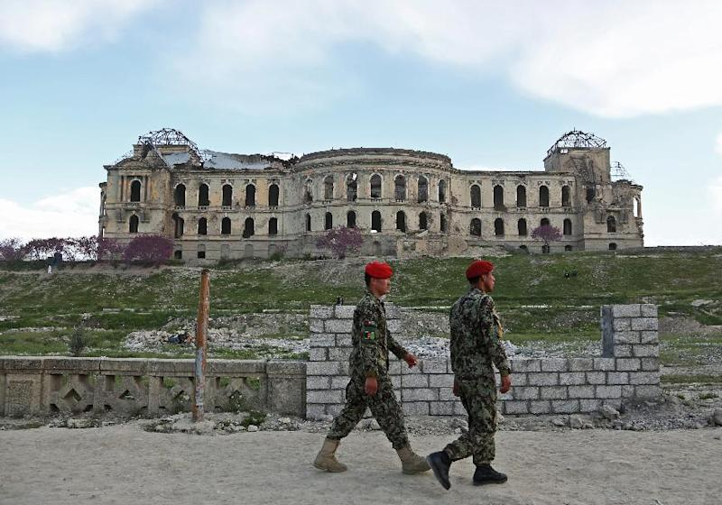 Afghan national army soldiers walk past the palace of the late King Amanullah Khan, which was destroyed during the civil war in early 1990s, in Kabul, Afghanistan, Sunday, April 27, 2014. (AP Photo/Rahmat Gul)