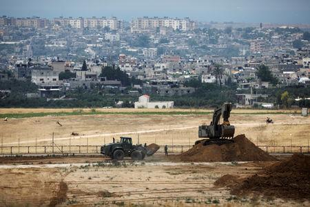 FILE PHOTO: Israeli bulldozers work on a position on the Israeli side of the border fence between Israel and the Gaza Strip