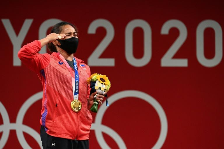 An emotional gold medallist, Hidilyn Diaz, salutes during the anthem after winning the 55kg weightlifting