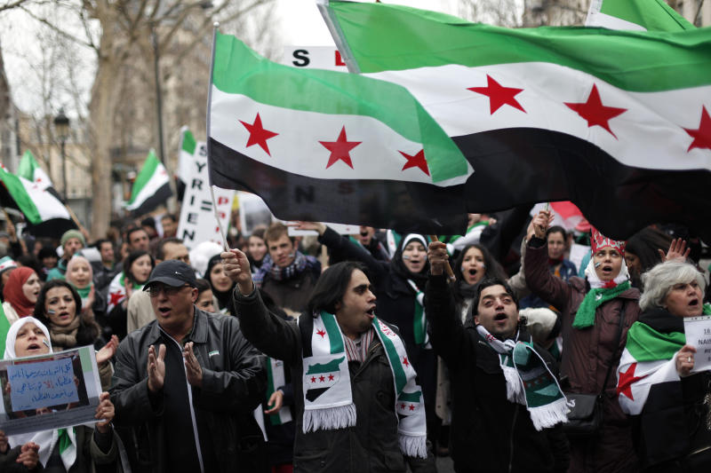 Demonstrators wave Syrian flags as they chant slogans during a march to mark the second anniversary of the revolt against the Syrian government of President Bashar Assad, in Paris, Saturday, March 16, 2013. The French President Francois Hollande said Thursday his country and Britain are pushing the European Union to quickly lift its arms embargo on Syria so that they can send weapons to rebel fighters. (AP Photo/Thibault Camus)